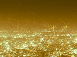 City landscape with gold lights and digital connectivity lines connecting the buildings