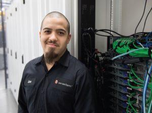 ServerFarm IT staff standing next to a server rack inside of Chicago data center